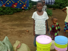 Child next to buckets of foodstuff