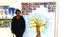 Staff nurse standing in front of a photograph and family tree display