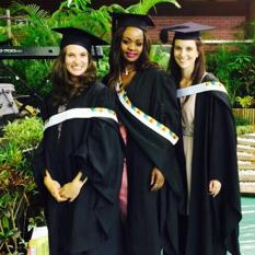 Three young women in gowns and mortar boards at Graduation