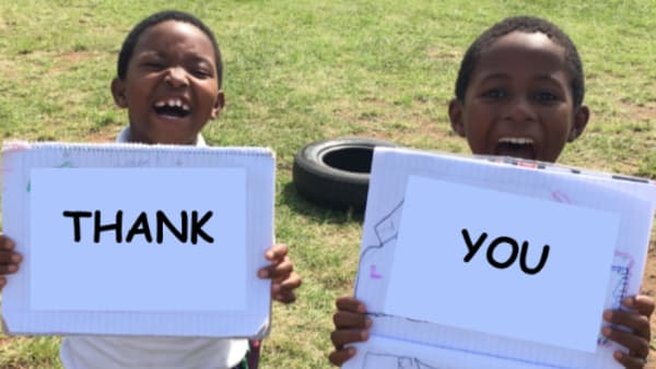 two children holding the words thank you