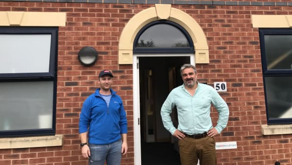 two men standing in front of a brick built office