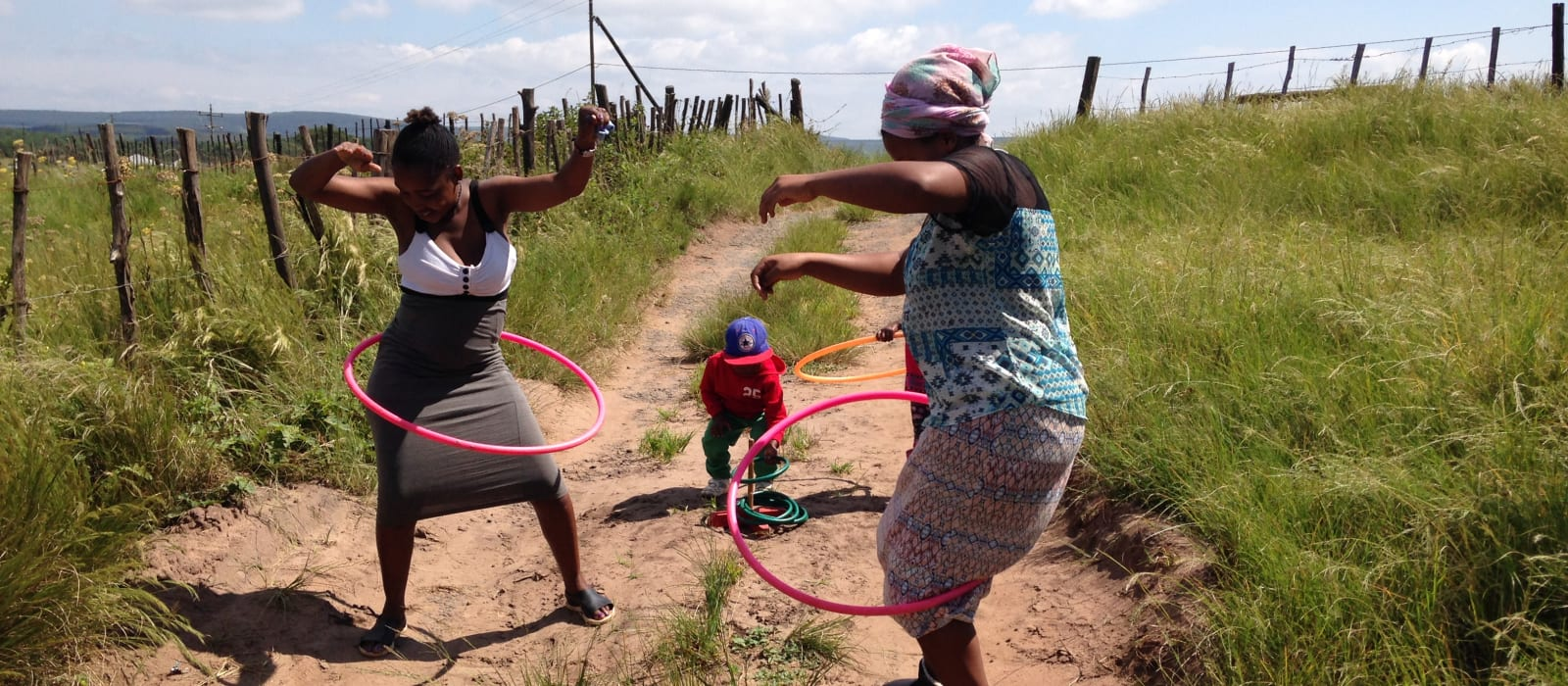 Two women hula hooping on rural track