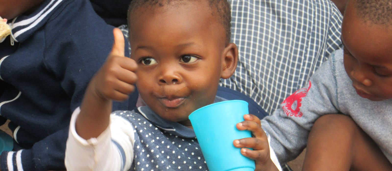 Child with a thumbs up, drinking from a blue cup