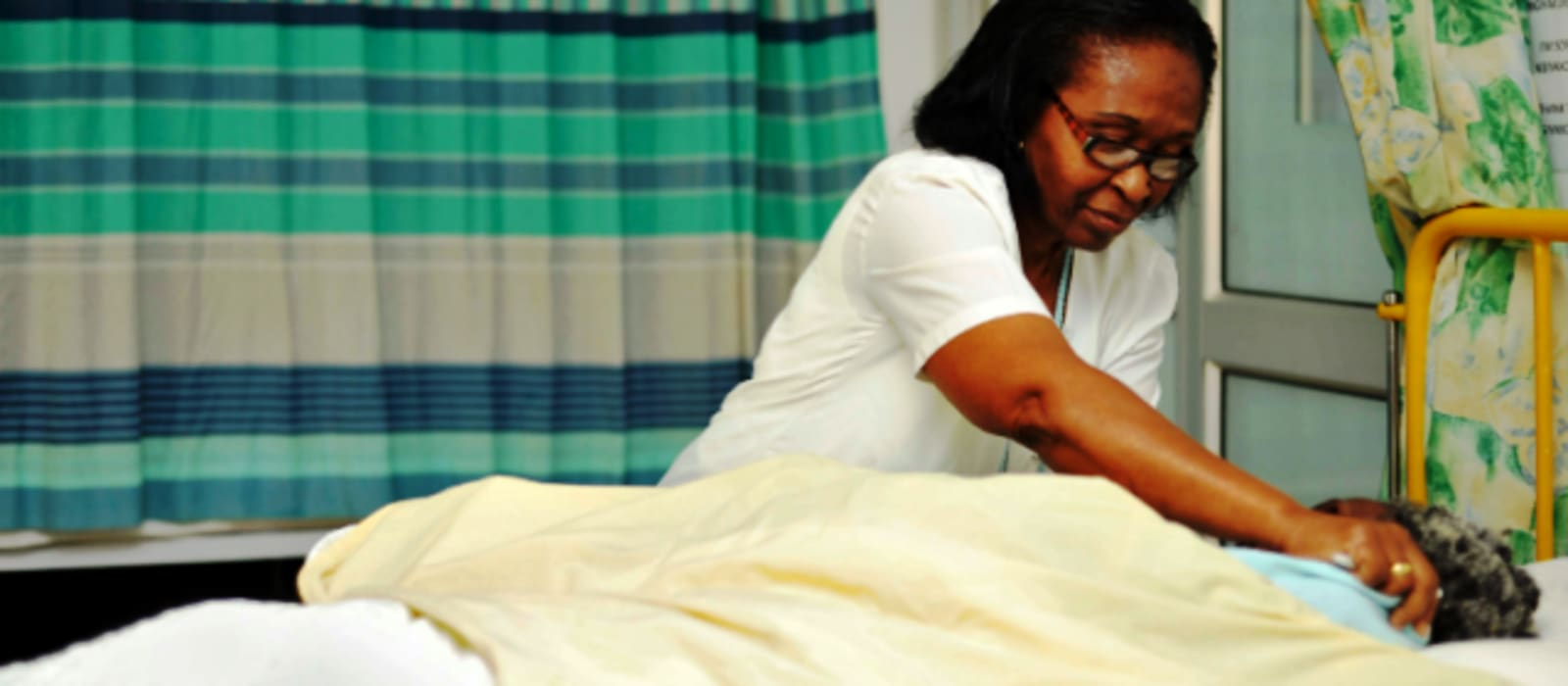 Healthcare worker arranging a blanket across a patient in bed